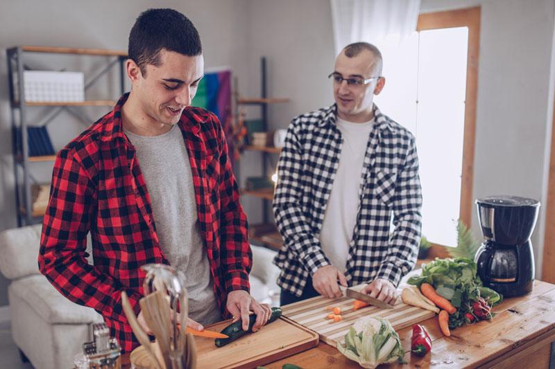 Kaksi miestä pilkkoo porkkanoita vierekkäin.