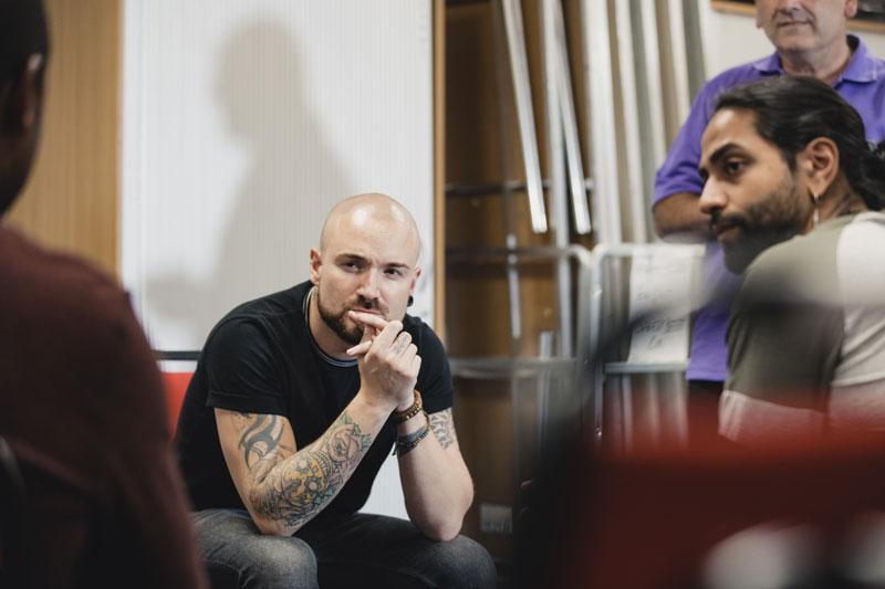 Miehet istuvat ringissä ja kuuntelevat tarkkaavaisesti.