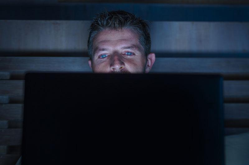 Mies katsoo pimeässä tietokoneen ruutua.