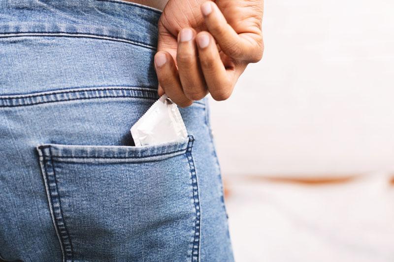 Mies ottaa takataskusta kondomin.