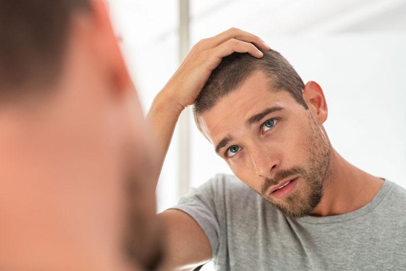 Mies katsoo itseään peilistä.