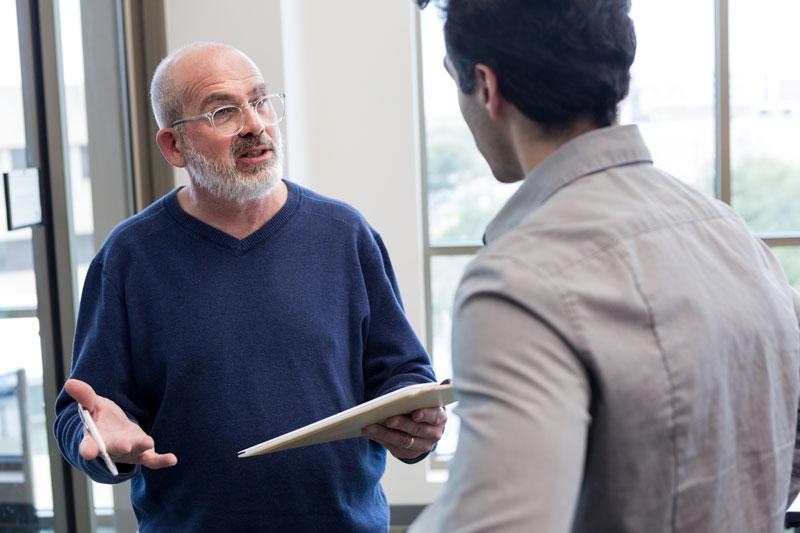 Vanhempi mies puhuu toiselle miehelle.