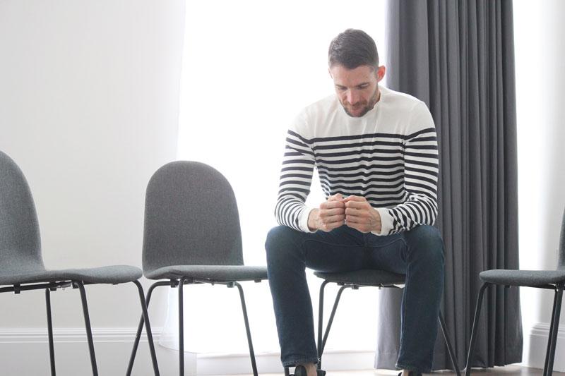 Mies istuu yksin penkillä ja tuijottaa käsiään.