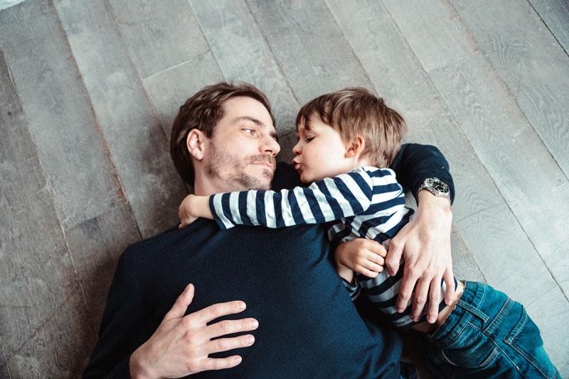 Isä ja poika makaavat lattialla.