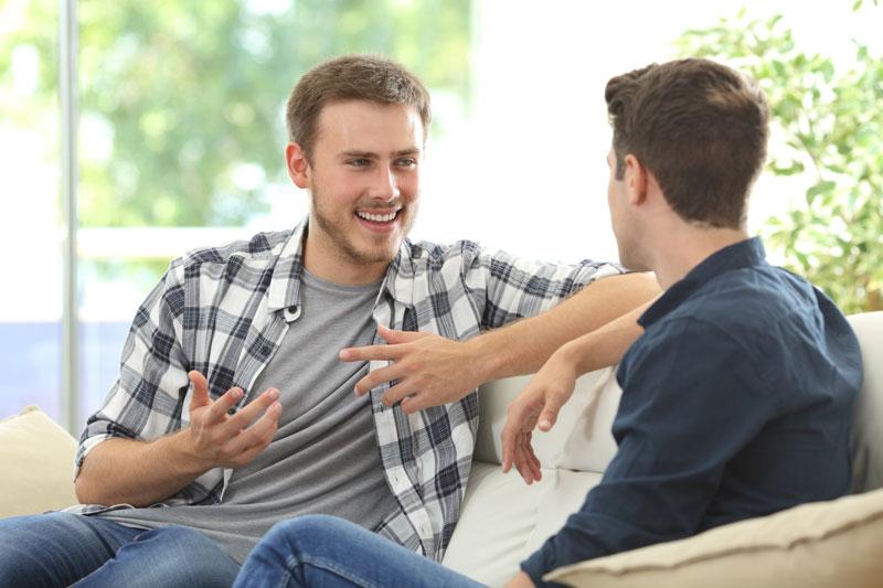 Mies juttelee iloisesti toisen miehen kanssa.