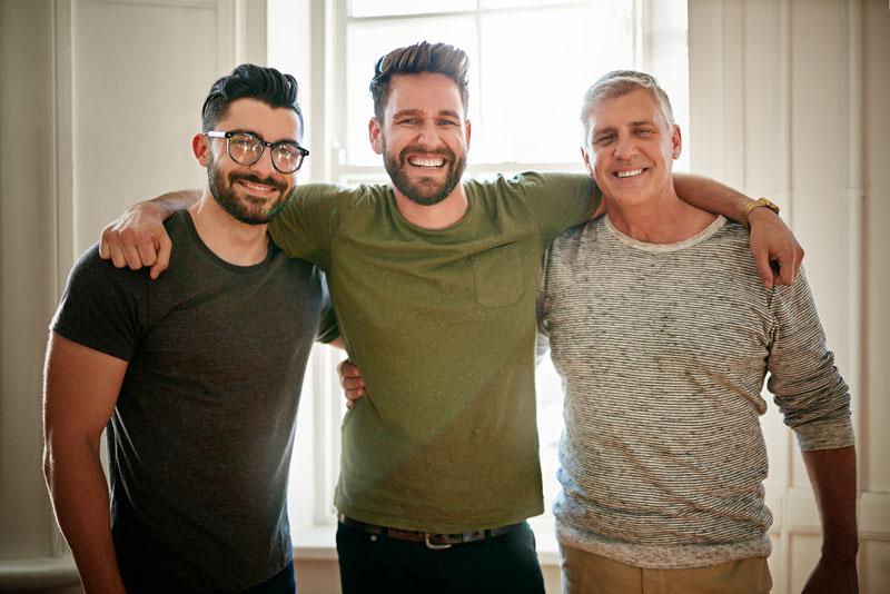 Kolme miestä seisovat vierekkäin ja katsovat hymyillen kameraan.