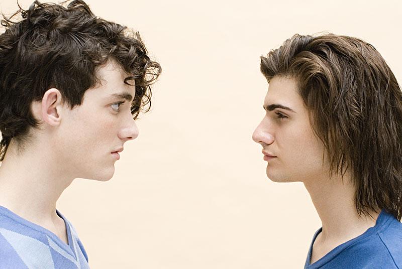 Kaksi miestä tuijottaa toisiaan silmiin.