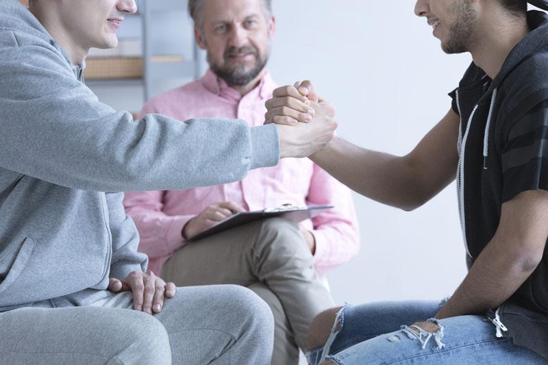 Kaksi miestä kättelevät, taustalla vanhempi mies seuraa tilannetta.