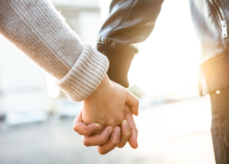 Kaksi henkilöä pitävät toisiaan käsistä kiinni.